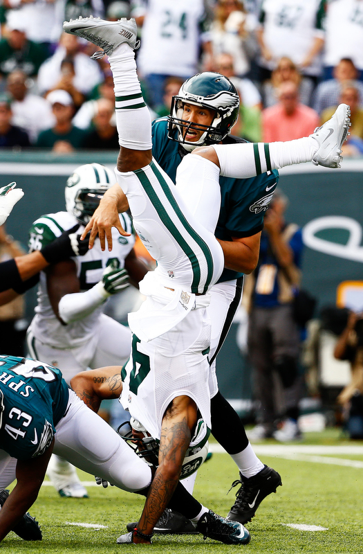 EAST RUTHERFORD, NJ - SEPTEMBER 27:   Buster Skrine #41 of the New York Jets flips upside down as he defends against  Sam Bradford #7 of the Philadelphia Eagles in the second quarter at MetLife Stadium on September 27, 2015 in East Rutherford, New Jersey.