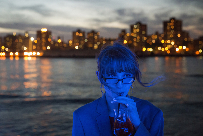 Blue View On The BoatA girls takes a sip of fruit punch while on the top deck of the Aqua Azul boat while being illuminated blue by the boat's deck lights. The Lakewood High School Prom held on the Aqua Azul boat, sails around the Hudson and East Rivers and New York Harbor.  Sunday June 7, 2015. Weehawken, NJ, USA