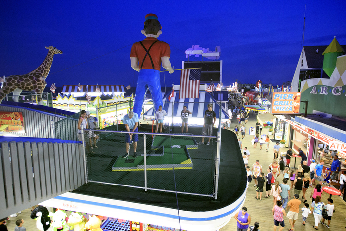 Miniature Golf Above The Boardwalk - Members of the Brooke and Monroe families play miniature golf above the boardwalk.  The Seaside Heights boardwalk area at night is thriving.  Sunday July 26, 2015. Seaside Heights, NJ, USA