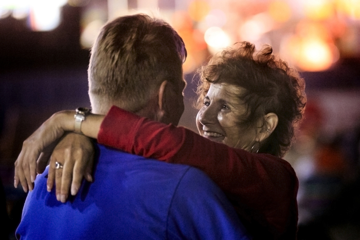 Love Is Still Strong - Tom looks into the eyes of Linda as the two embrace while on the beach listening to the Rolling Stones cover band The Glimmer Twins perform as part of the Throwback Thursday concert series. The Seaside Heights boardwalk area at night is thriving.  Thursday July 16, 2015. Seaside Heights, NJ, USA