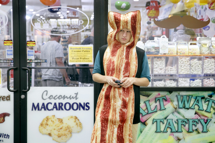 Bacon Boy - Jonathan Vogel, 15, of Toms River, NJ, takes a break looking at his iPhone as he watches people along the boardwalk outside the the Sweet Shop candy store. He works for the store dressed as Bacon Boy a couple nights a week. The Seaside Heights boardwalk area at night is thriving.Friday July 24, 2015. Seaside Heights, NJ, USA