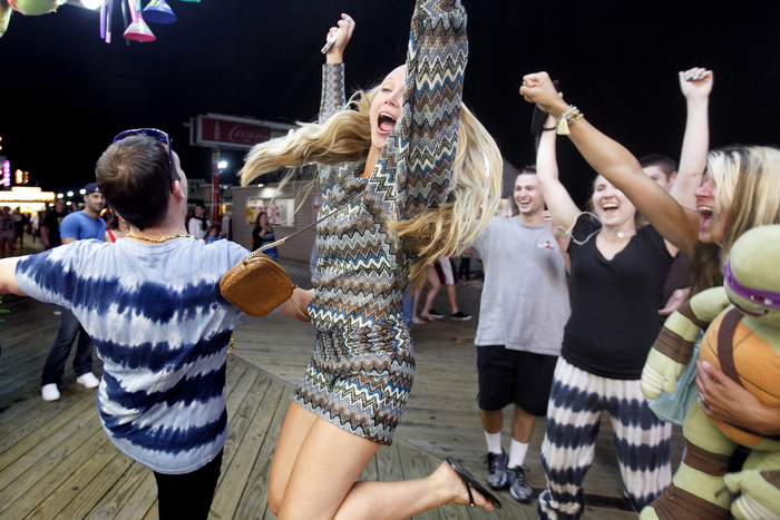 Big Winners - Ryan Klink, left, of Exter, NH, celebrates with relatives after he won and through a football into a tire at a boardwalk game. The Seaside Heights boardwalk area at night is thriving.Friday July 24, 2015. Seaside Heights, NJ, USA