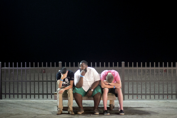 Partied Out - Late at night on the boardwalk a friend sits in between a pair that wasn't feeling their best after spending the night partying at Spicy Cantina boardwalk bar and grill. The Seaside Heights boardwalk area at night is thriving.Friday July 24, 2015. Seaside Heights, NJ, USA