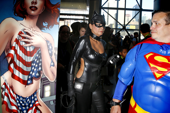 Americana, Catwoman and Superman -  People walk by an advertisement for Double Take Comics while outside the exhibit hall. Fans from all around attended the 4th and last day of New York Comic-Con 2015 which is being held at the Jacob Javits Center. Some attended object to the sexist tone of some of the displays while others ignore it. Sunday October 11, 2015. New York, NY, USA