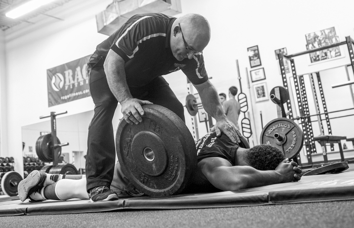 Strength trainer Joe McAuliffe comes to the aid of 8th grader Josh McKenzie after McKenzie collapsed while doing plank exercises with a 45-pound plate on his back.