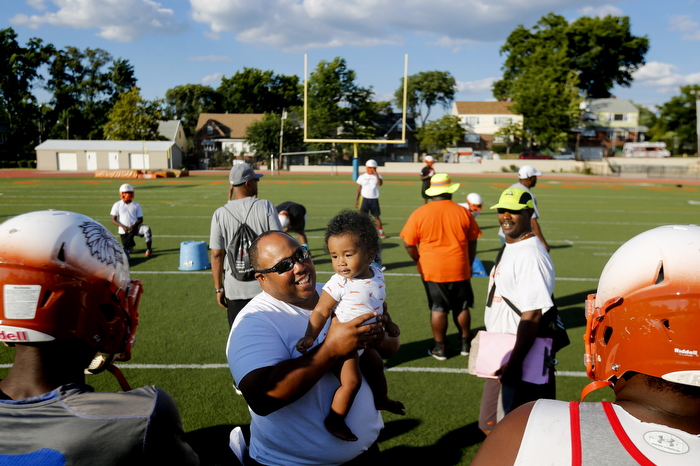 Family - Weequahic head coach Brian Logan holds his grandson Cameron Logan during a break in practice. Logan has stressed that the team be a family.  Wednesday August 26, 2015. Newark, NJ, USA