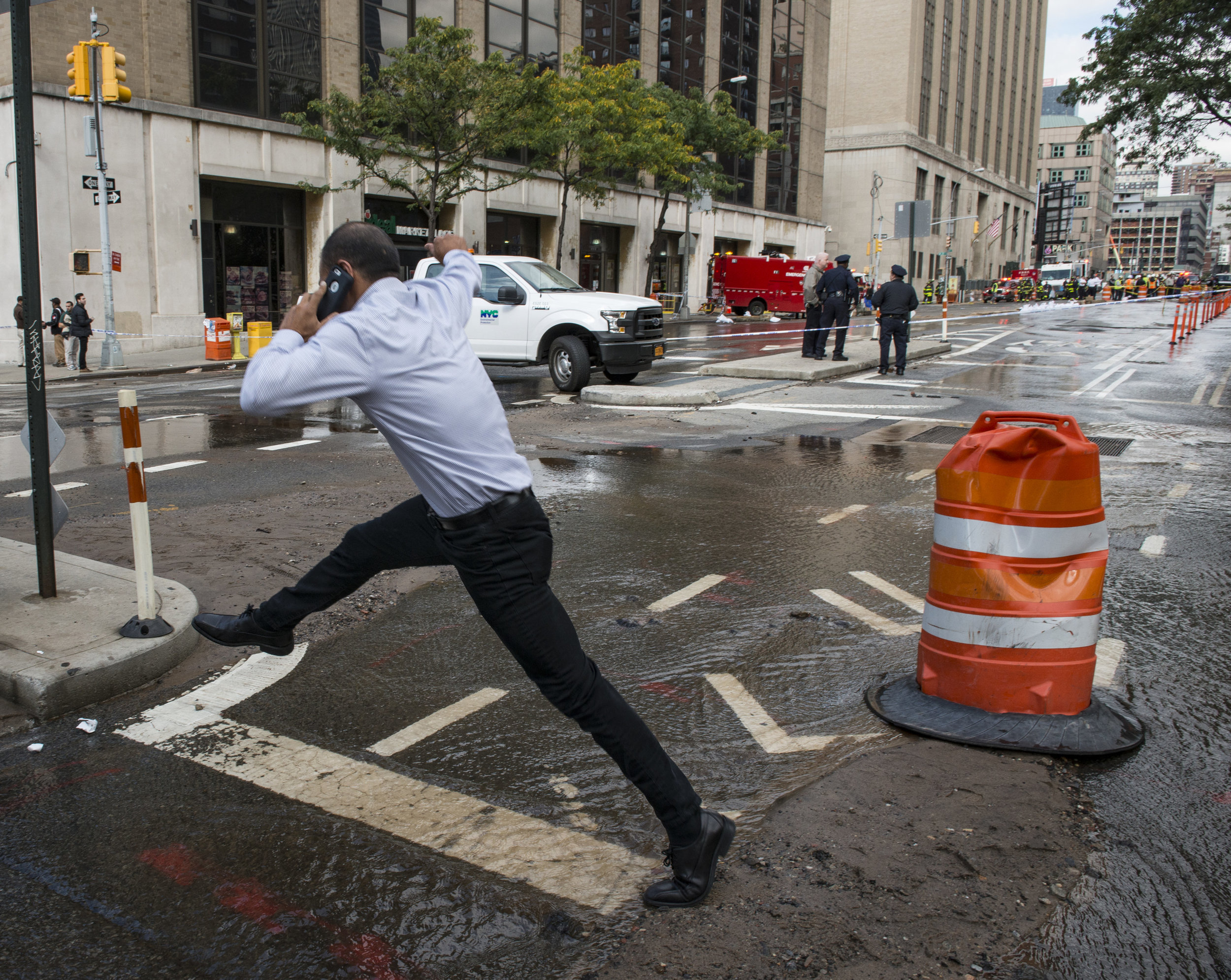 Exhibit AwardAnthony Demundo/Daily News  PUDDLE JUMPERA pedestrian jumps to get across the flowing water as emergency responders work the scene of a water main break at the corner of 9th Avenue and West 29th Street in Manhattan on Wednesday, October 12, 2016.
