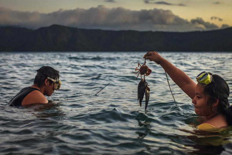 Jan. 13, 2016 - Laguna de Apoyo, Nicaragua: A man and woman spearfishing at dusk in Laguna de Apoyo, a volcanic lake near Masaya, Jan. 13, 2016. Nicaragua, the second poorest country in the Western Hemisphere after Haiti, has been hard hit by climate change and drought but sustainable farming and irrigation projects have given some communities a means of survival.