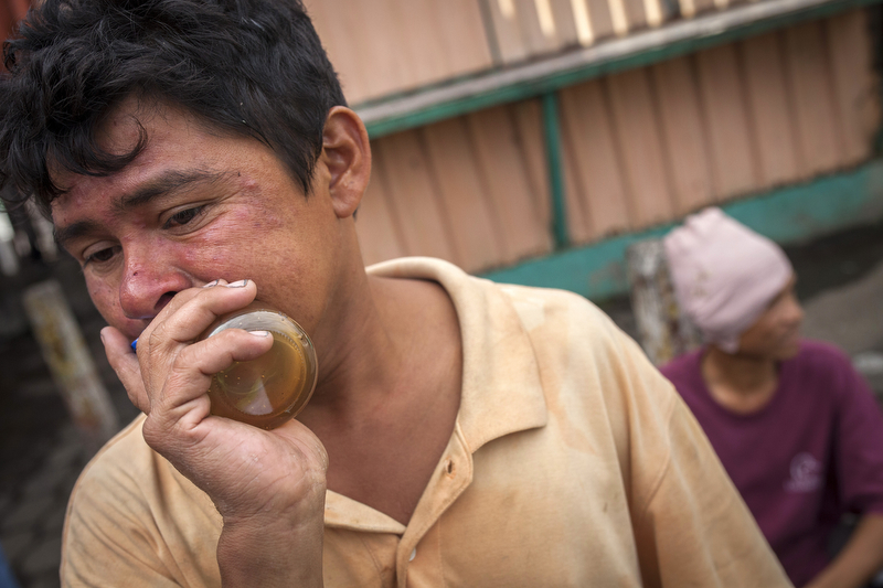 Jan. 18, 2016 - Managua, Nicaragua: Cesar Cruz, 25, inhales glue from a glass bottle in the Oriental Market in Managua, Jan. 18, 2016. According to Inhijambia, a community organization providing upport services to at-risk children, the glue is made from gasoline and toluene and is extremely cheap and capable of causing severe neurological damage.