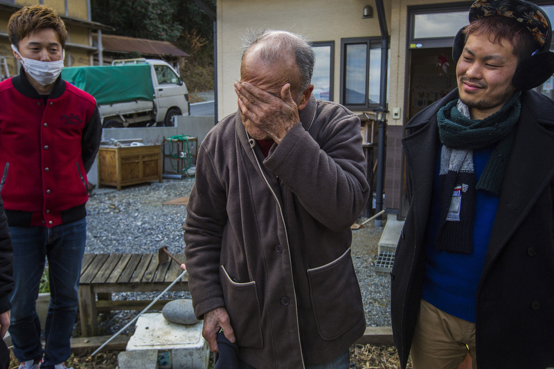 (Summary)Naoshi Sato, 82, lost his son, Shoichi, when the earthquake and the tsunami hit Japan in March 2011. His old house, where he had lived his entire life, was badly damaged. Even though most survivors fled to evacuation centers and settled into temporary houses, he chose to remain in his half-destroyed house living amid debris, without electricity or running water. Naoshi believed that he had to be there for his dead son. His wife, Teruko, 77, and Shoichi�s wife, Mio, 48, followed his spirit at the beginning, and they huddled together on what remained of their family plot for four months. But the Satos� misery over losing Shoichi consumed them. They are now in the midst of a painful separation after five decades of marriage, and they have cut their grief-stricken daughter-in-law out of their lives entirely.(Caption)Naoshi bursts in tears outside his house in Kesen, March 11, 2016, on the fifth anniversary of the earthquake and the tsunami after seeing visitors. They visited Naoshi as disaster volunteers five years ago, and their sudden appearance reminded him his extraordinary hard life he had for past five years. As an old man living by himself for a long time, he welcomes visitors to his home and to Kesen.