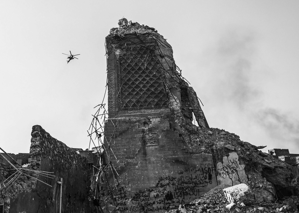 A coalition attack helicopter flies past the rubble of the 12th century Al Hadba minaret of the Al Nuri Mosque, which was blown up by ISIS, as they continue fire on remaining ISIS positions in the Old City of Mosul, Iraq, on July 12, 2017. Days after the Iraqi government declared the Islamic State was defeated in Mosul, heavy fighting persisted while newly liberated residents still fled the Old City neighborhood in droves. With temperatures reaching 115 degrees, many needed medical attention for heat exhaustion.