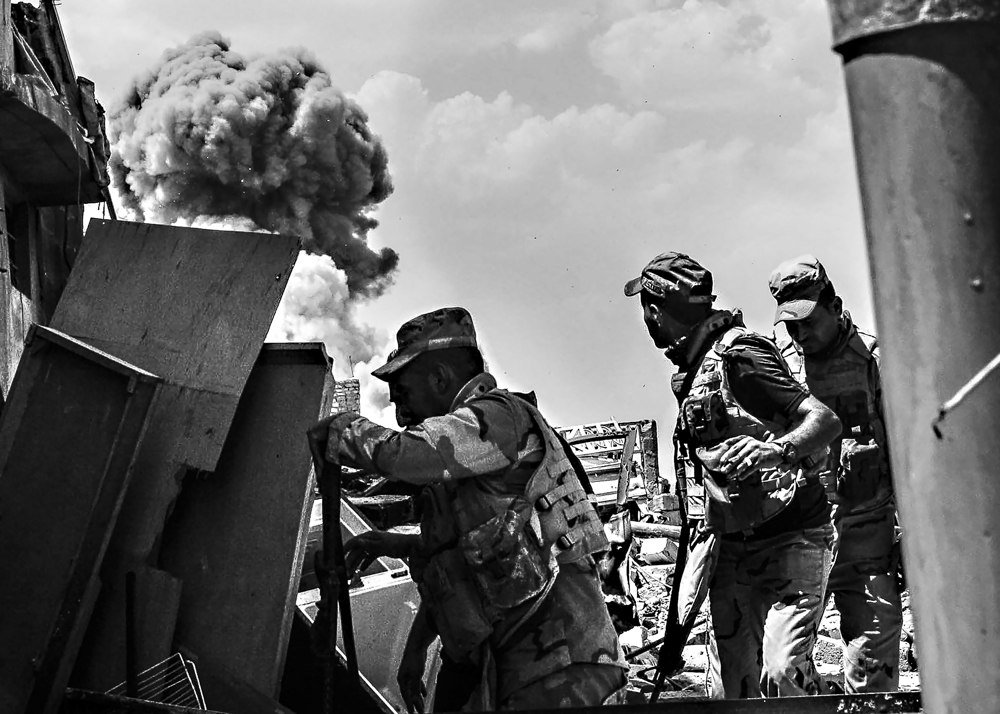 Iraqi Army soldiers take cover to avoid shrapnel from an airstrike at the front lineof the  Midan neighborhood, in the Old City in Mosul, Iraq, July 13, 2017.  Days after the Iraqi government declared the Islamic State was defeated in Mosul, heavy fighting persisted while newly liberated residents still fled the Old City neighborhood in droves. With temperatures reaching 115 degrees, many needed medical attention for heat exhaustion.