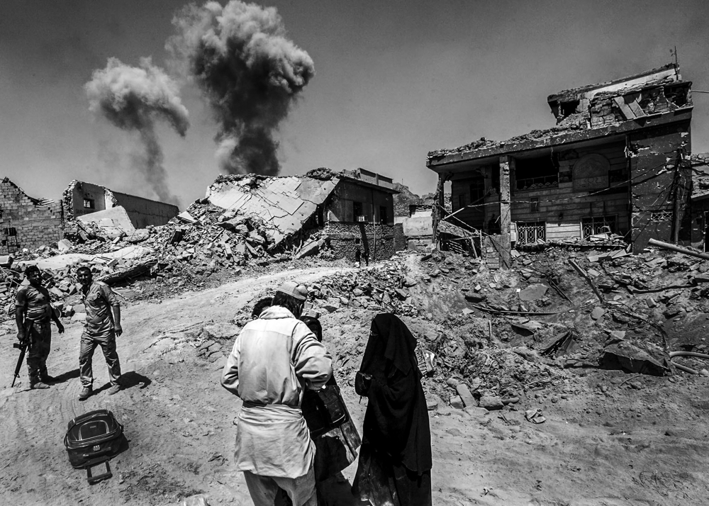Coalition airstrikes and incoming mortar rounds from ISIS land meters away as civilians flee the militant-held territory under cover of the Iraqi Army while they work to push the remaining fighters of the terror group out of the city on June 30, 2017. A day after the Iraqi government declared the Islamic State was defeated in Mosul, heavy fighting persisted while newly liberated residents still fled the Old City neighborhood in droves. With temperatures reaching 115 degrees, many needed medical attention for heat exhaustion.