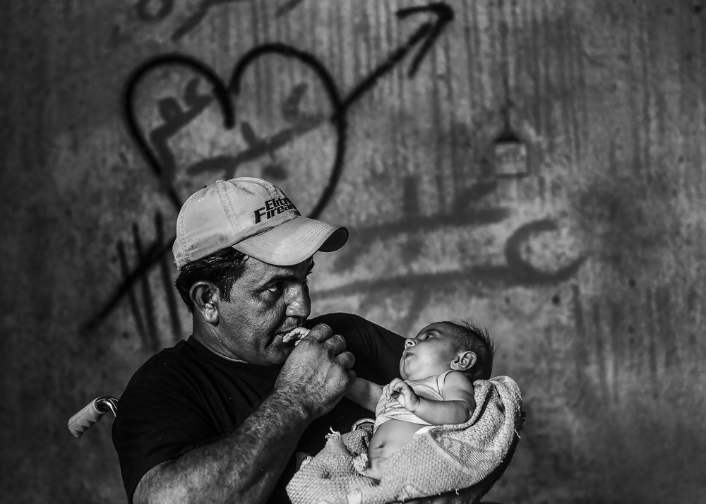 ISOF CSM Maitham Jawad comforts Sadra, two months and four days old, as her mother is pumped with vitamins from an IV at a field clinic kilometers from the front line on July 2, 2017.  Days after the Iraqi government declared the Islamic State was defeated in Mosul, heavy fighting persisted while newly liberated residents still fled the Old City neighborhood in droves. With temperatures reaching 115 degrees, many needed medical attention for heat exhaustion.
