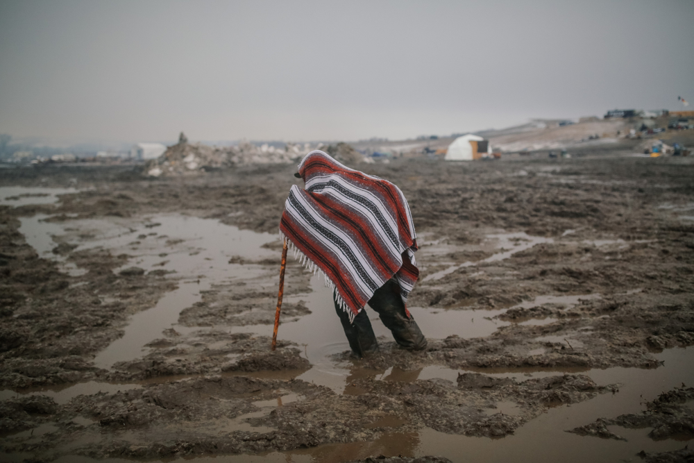 February 22, 2017: Cannonball, ND - A man walks through the mud. The camp emptied in anticipation of a raid by law enforcement. Led by the Standing Rock Sioux tribe to protest the Dakota Access Pipeline, the camp was dismantled by authorities the next day.