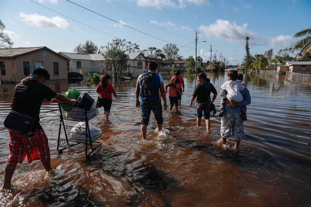 September 12, 2017: Immokalee, FL - Families gather supplies after their neighborhood was flooded by Hurricane Irma. The town of Immokalee, home to migrant farm workers and immigrants from Haiti and Latin America, was one of the hardest hit by Hurricane Irma.