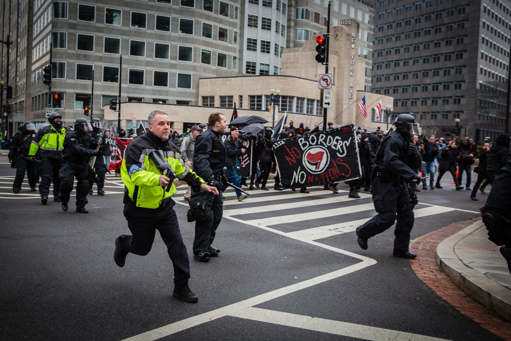 Police chase Black Bloc anarchist protestors with pepper spray during the mayhem on Inauguration Day near Franklin Square on January 20, 2017 in Washington, DC, USA.