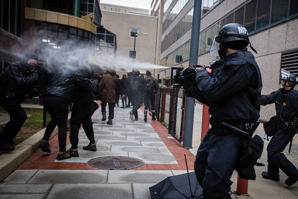 A police officer dressed in riot gear pepper sprays Black Bloc anarchist protestors during the mayhem on Inauguration Day near Franklin Square on January 20, 2017 in Washington, DC, USA.