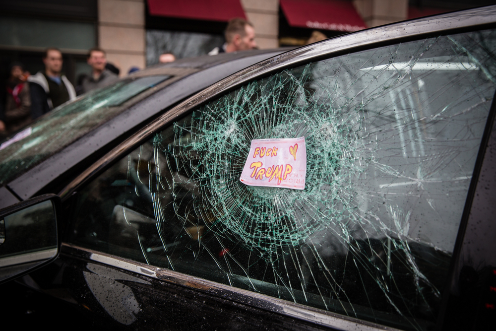 """A note reads """"Fuck Trump"""" on a smashed window of a limousine during the mayhem on Inauguration Day near Franklin Square on January 20, 2017 in Washington, DC, USA.Thousands of people poured into Washington, DC to protest Donald Trump'sinauguration. Police arrested a total of 217 participants in the 'Disrupt J20'protest, and charged with felony rioting. Among them are journalists, nurses, and dozens of others who say they did nothing illegal."""