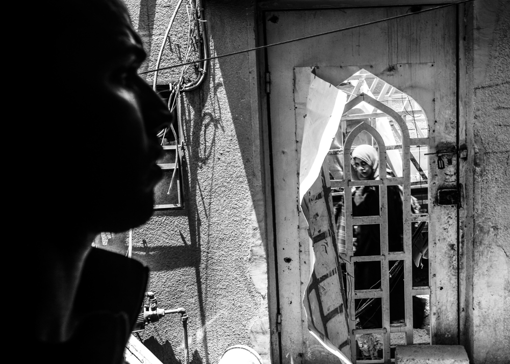 After hearing rumors of two females entering liberated territory with bombs strapped to their waists, ISOF CTS troops watch as newly liberated Mosul residents make their way through the Old City neighborhood on July 2, 2017.