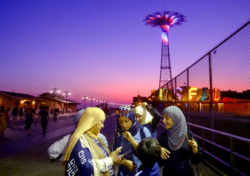 Boardwalk Evening Fun - A family enjoys a summer evening on the Coney Island boardwalk.  Sunday September 24, 2017. Brooklyn, NY, USA