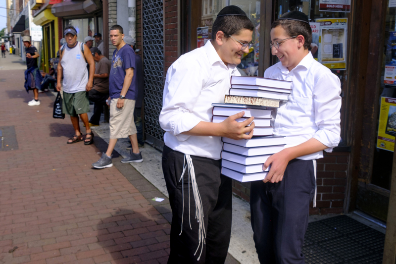 Two Communities - A pair of Orthodox teenagers carry books  on a busy sidewalk along 2nd Street. Sunday July 23, 2017. Lakewood, NJ, USA