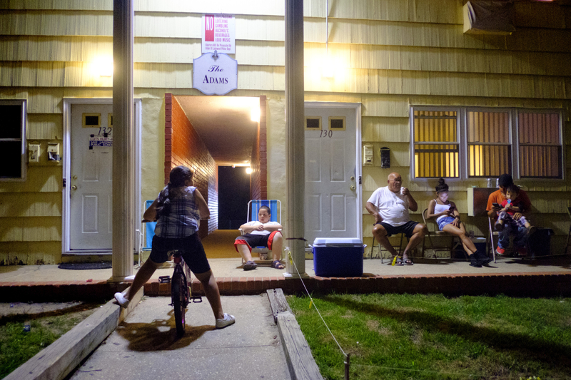 Remaining Families on MLK - Residents of the Lakewood Plaza Apartments on MLK Blvd. socialize outside on a Friday night. Most of the street's homes has been bought by Orthodox families and have knocked down and rebuilt over those houses.    Friday July 21, 2017. Lakewood, NJ, USA