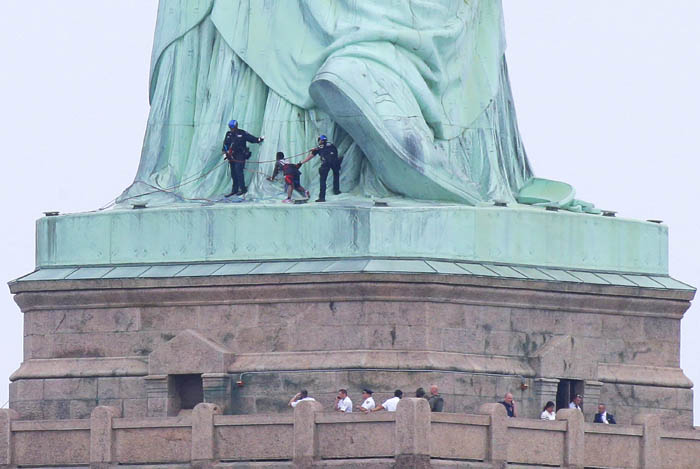 Authorities watch as a protester is removed from the base of the Statue of Liberty on Independence Day on July 4, 2018 in Jersey City, New Jersey. Protester Patricia Okoumou says her four-hour standoff with police was fired by outrage at Trump's caging of migrant children. At least six protesters were arrested at the monument earlier in the day.