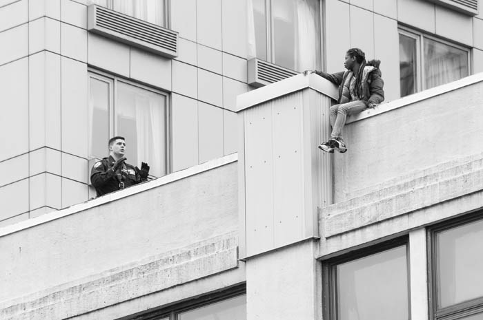 An NYPD Emergency Service Unit officer speaks to a female jumper sitting on a ledge on the roof of 121 6th Avenue in Manhattan on April 4, 2018. The woman was safely removed from the ledge.