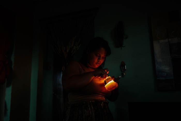 February 12, 2018: Punta Santiago, Humacao Puerto Rico - Hennessy Del Valle, 18, lights a candle in the house she shares with her mother, whom she cares for. After a catastrophic hurricane, rates of mental illness continue to rise.