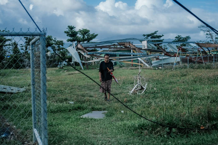 February 12, 2018: Punta Santiago, Humacao Puerto Rico - A woman walks by debris leftover from Hurricane Maria in Punta Santiago. Nearly 5 months after Hurricane Maria reached the island around 1/3 of Puerto Rico is still without power.  After a catastrophic hurricane, rates of mental illness continue to rise.