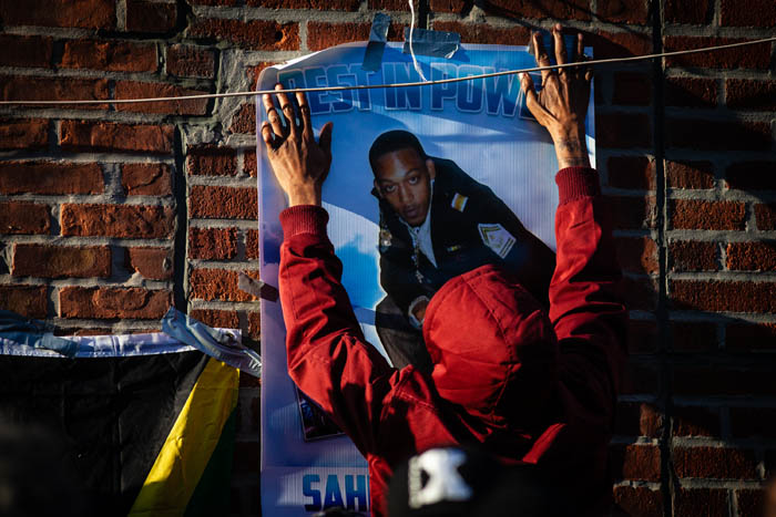 A man tapes a poster of Saheed Vassell to the wall by the corner of Utica Avenue and Montgomery Street in Crown Heights on April 5, 2018 in New York City, USA.  Plain clothed NYPD officers shot and fatally killed Saheed Vassell at this location the day before, after reports of a man in the area was carrying a gun. Vassell, had been carrying a small metal pipe.