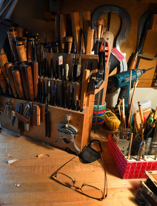 "Portrait of master violin maker Charles Rufino, 66, sitting in the light of a south-facing window at his carpet-covered workbench. The tools of his craft surround him. ""I'm trying to do this one thing well,"" he says, ""I enjoy the awareness when I'm working and shaping and cutting the wood. I'm the luckiest man I know.""  Charles has been crafting string instruments since 1974. April 4, 2018. 