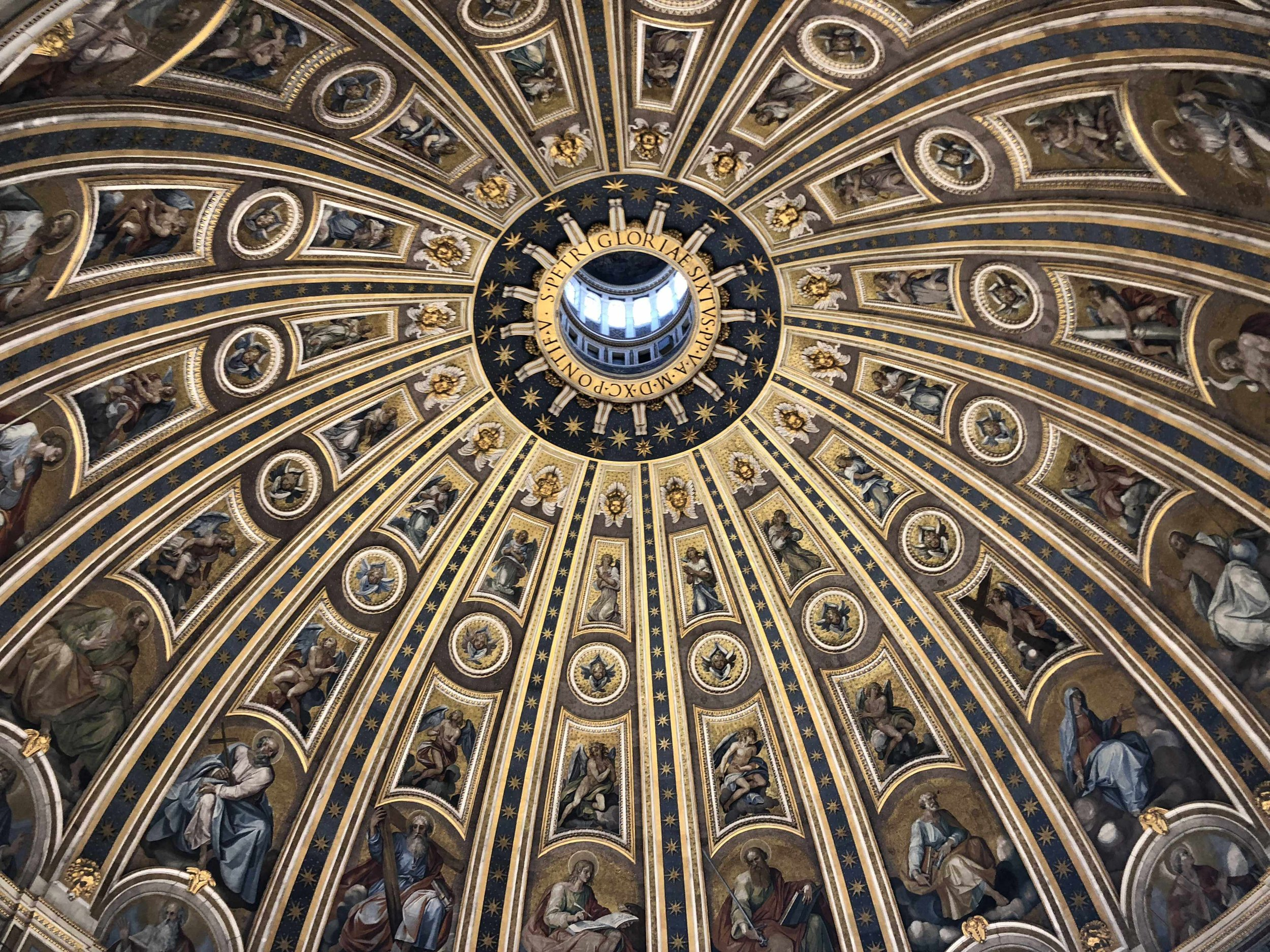 Completed in 1590, the interior of the Dome was dedicated the inner ring around the opening to Sixtus V. The Dome was concluded under the works of Giacomo della Porta and Domenico Fontana