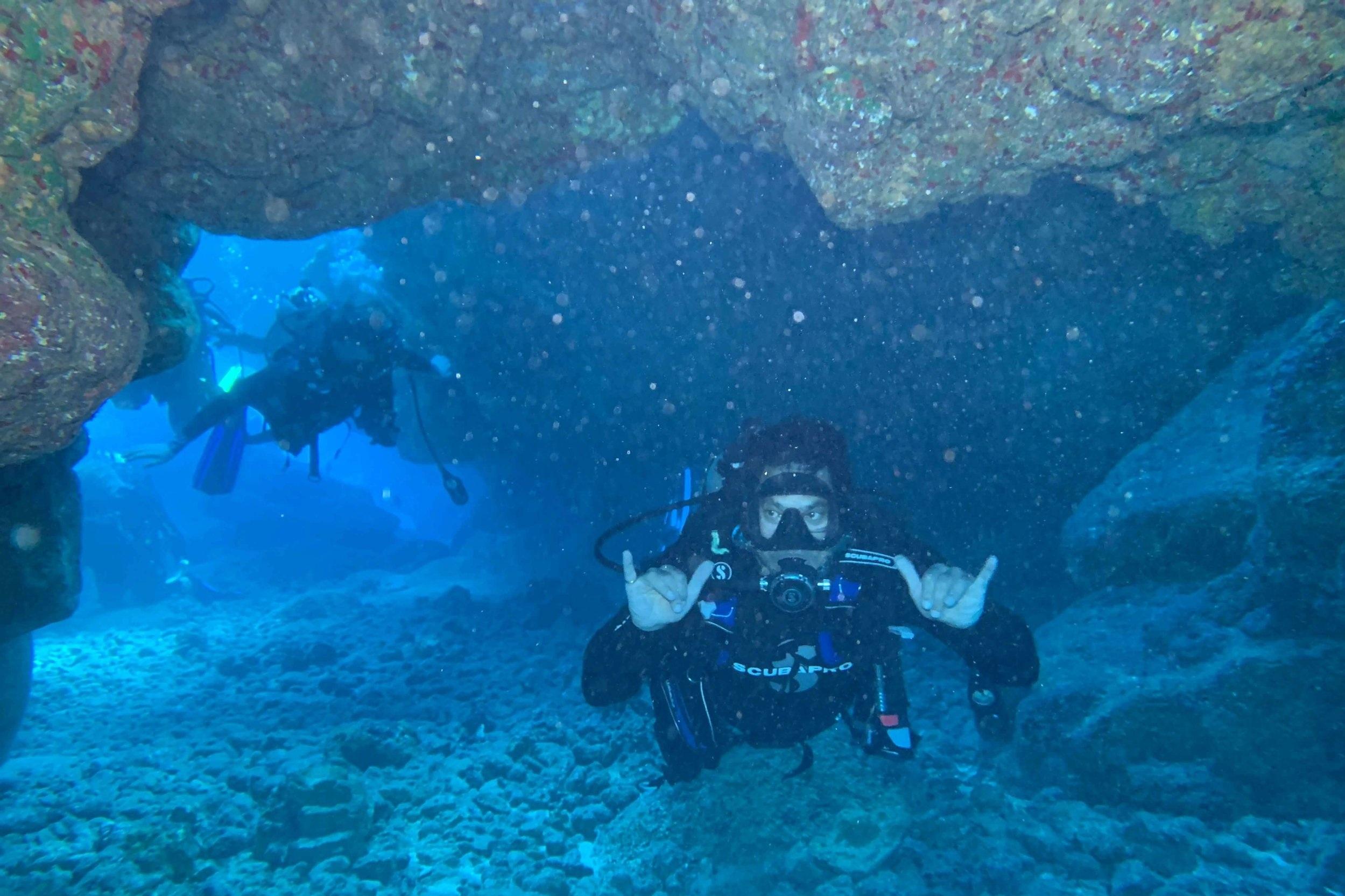 A diver swims through a spooky tunnel at Sheraton Caverns, Kauai. Photo credit: Josh Childress
