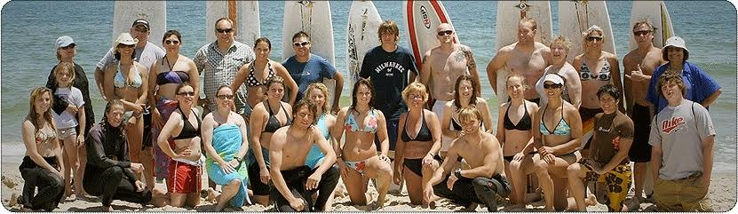 A group of surf students on the beach with their boards.
