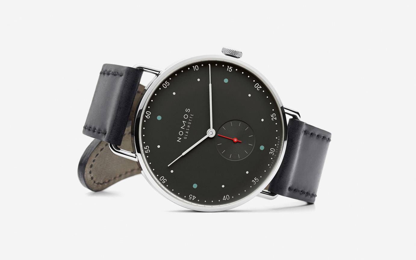The manual wind, no-date option is available with a 38 mm case with white or the black dial as shown. Click through to purchase directly from Nomos.