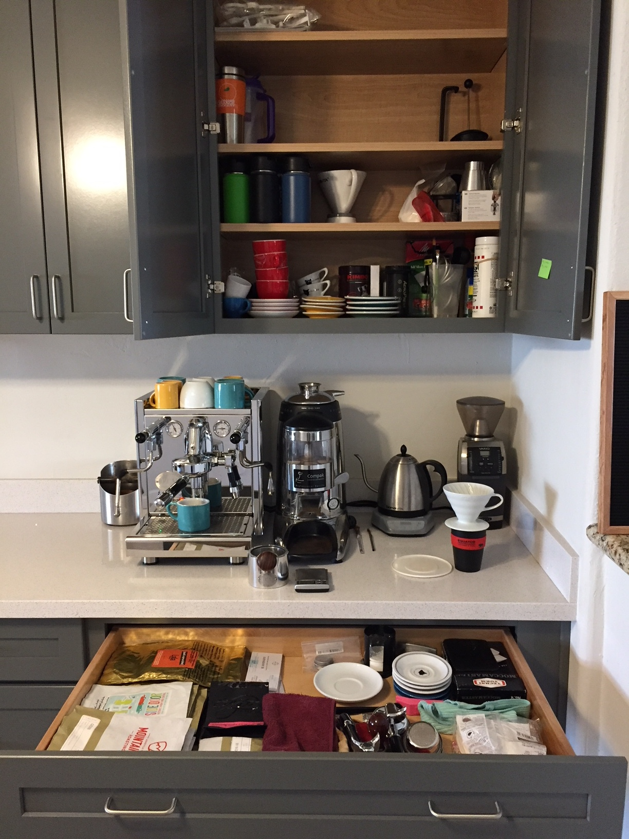 Cups, saucers, travel mugs, other brewers, detergents, brushes, and less used accessories in the cabinet above.