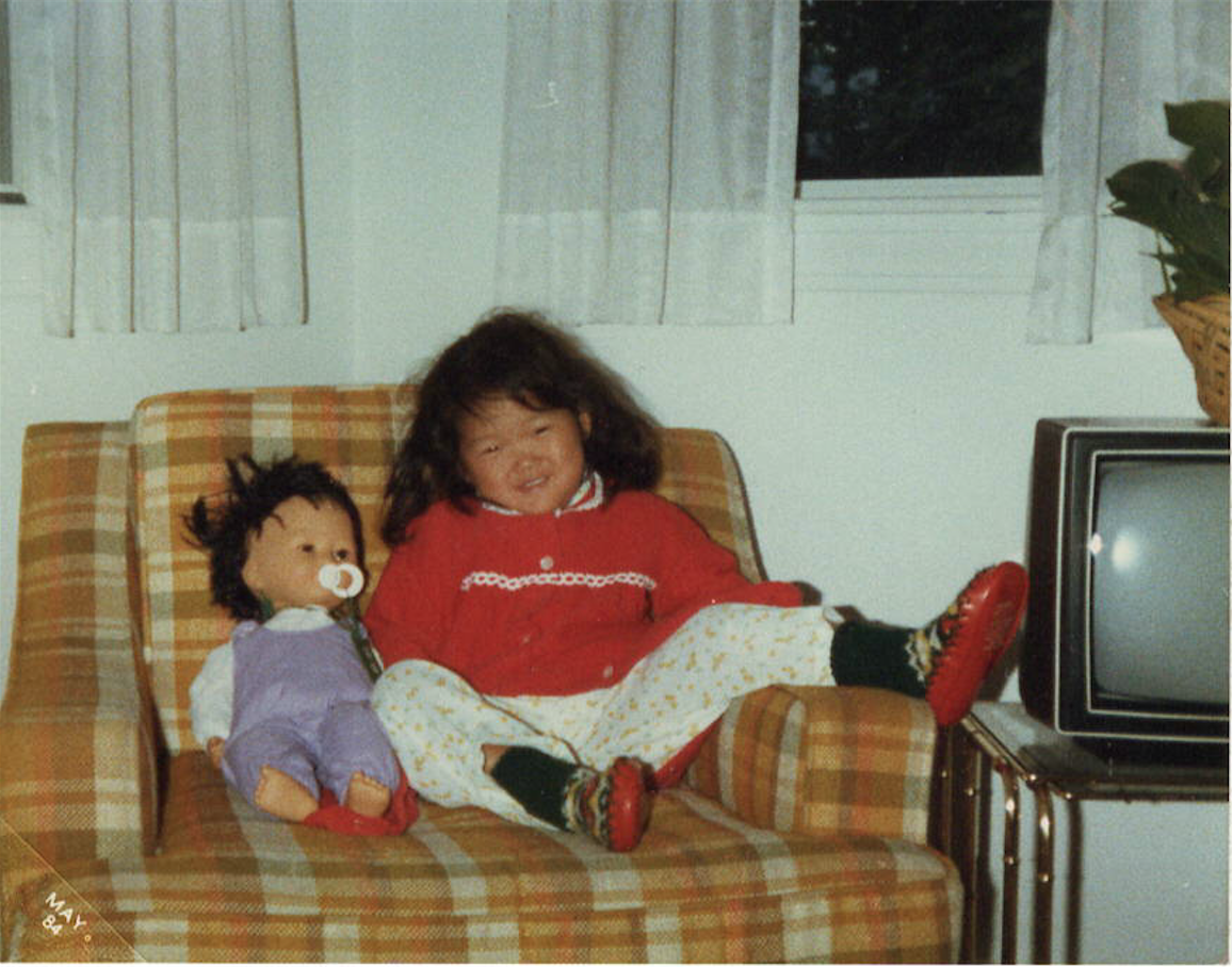 "One of my many ""looks"" I gave the camera. Once my cheeks smiled, my Asian eyes promptly disappeared. My Asian doll was aptly name Korea, after my birth country. Such a lady in that last photo of the triptych, aren't I?  Melrose, Massachussetts, circa 1983. Photo: Fox Family Archives/Whitney J. Fox Photography"