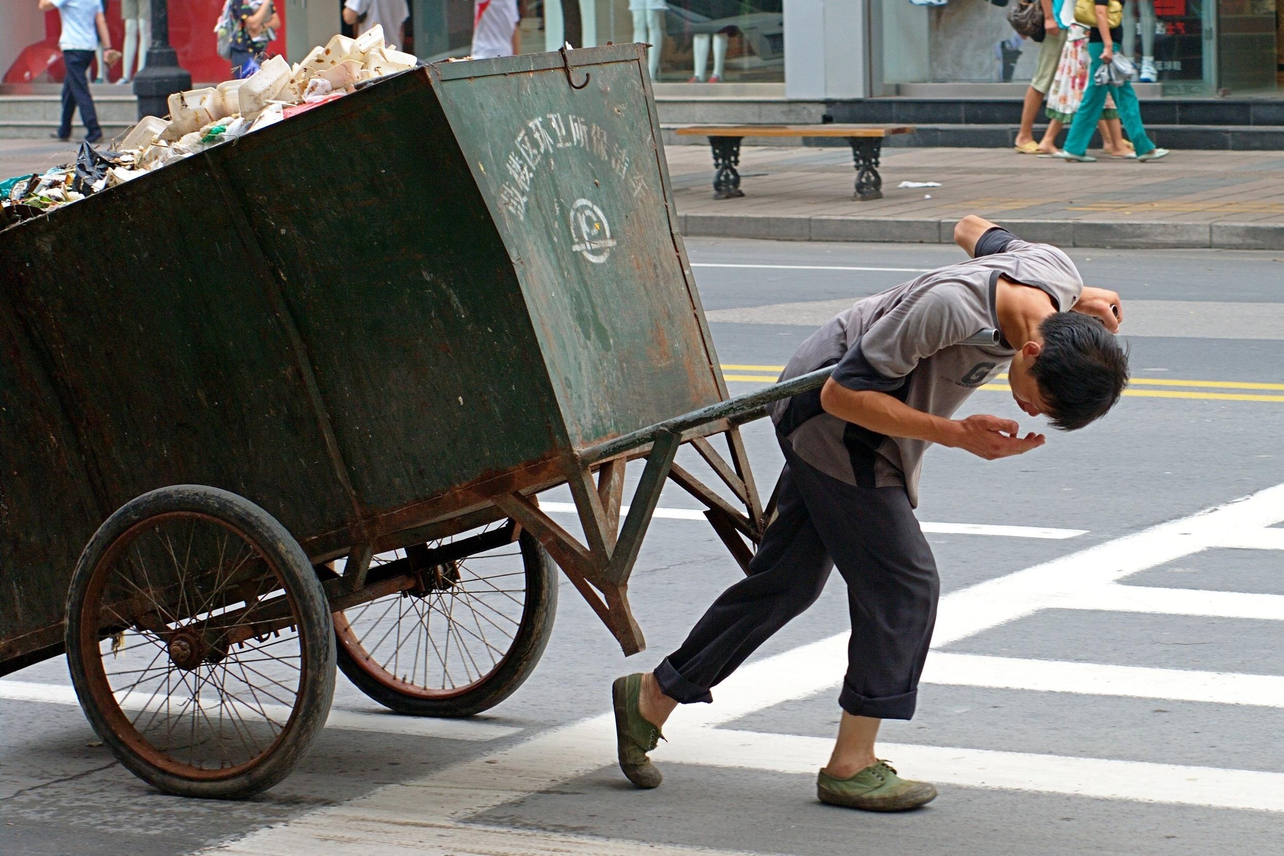A_man_is_suffering_pulling_a_trash.jpg