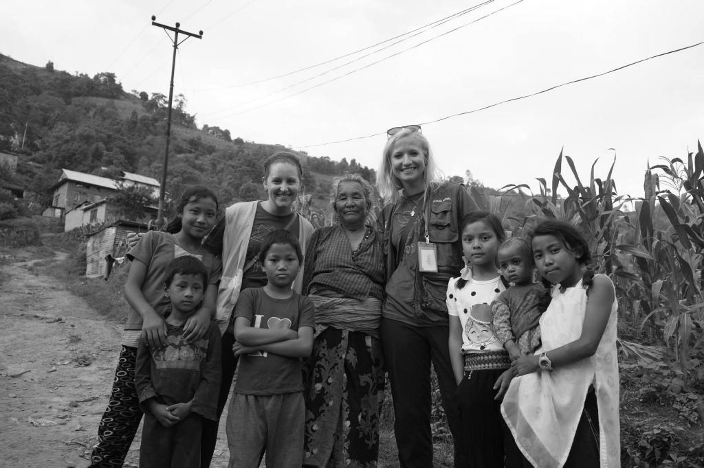 Michelle (top row, 2nd from left) and Erin (top row, 4th from left) at a medical distribution in Bhaktapur, Nepal, during a 2015 earthquake relief campaign.