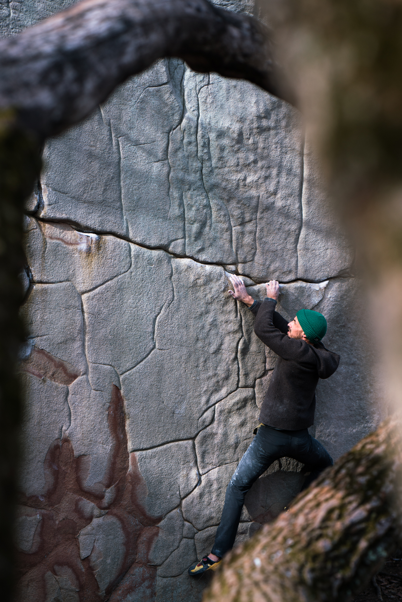 Matt Ginley with the green hat beta on a v10 traverse across the Deception Boulder