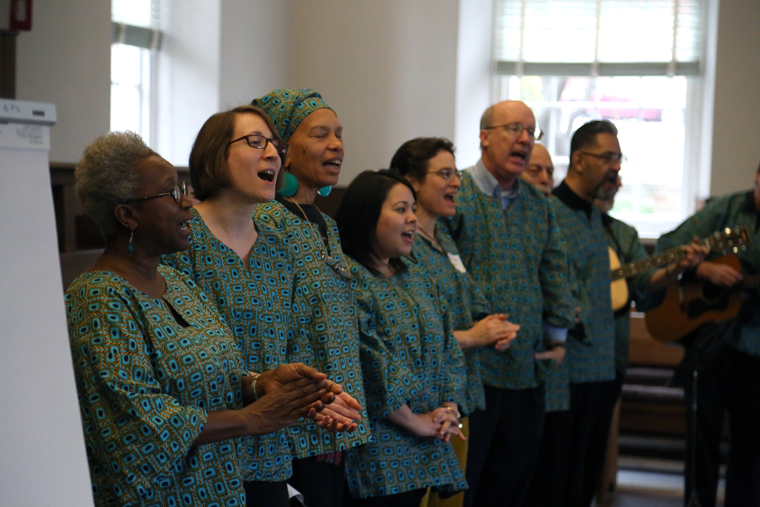 A multiracial group sings at the SURJ DC launch event. Photo by Eric Krupke