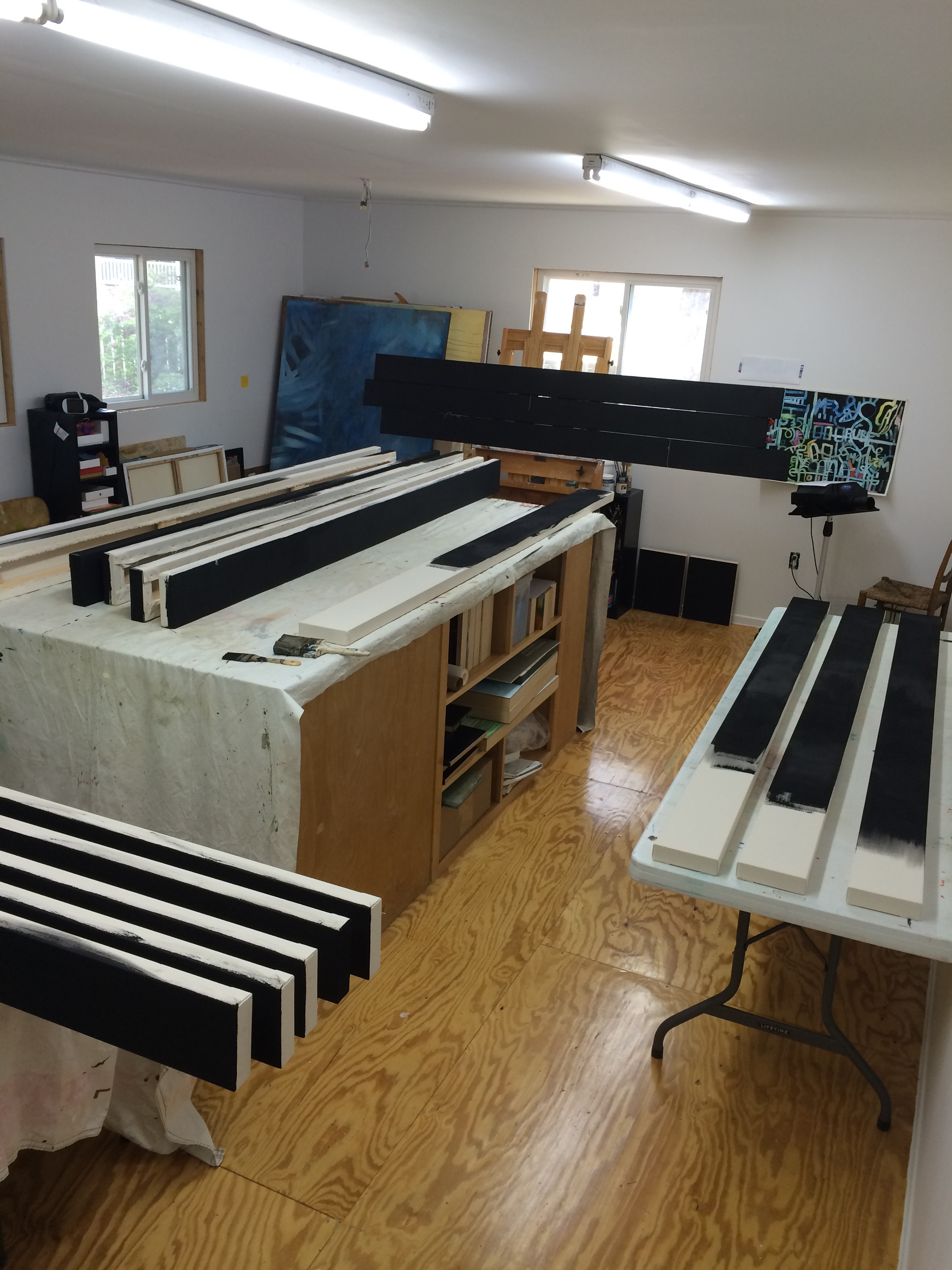"""18, 8'X6"""" canvases being gessoed with black gesso."""