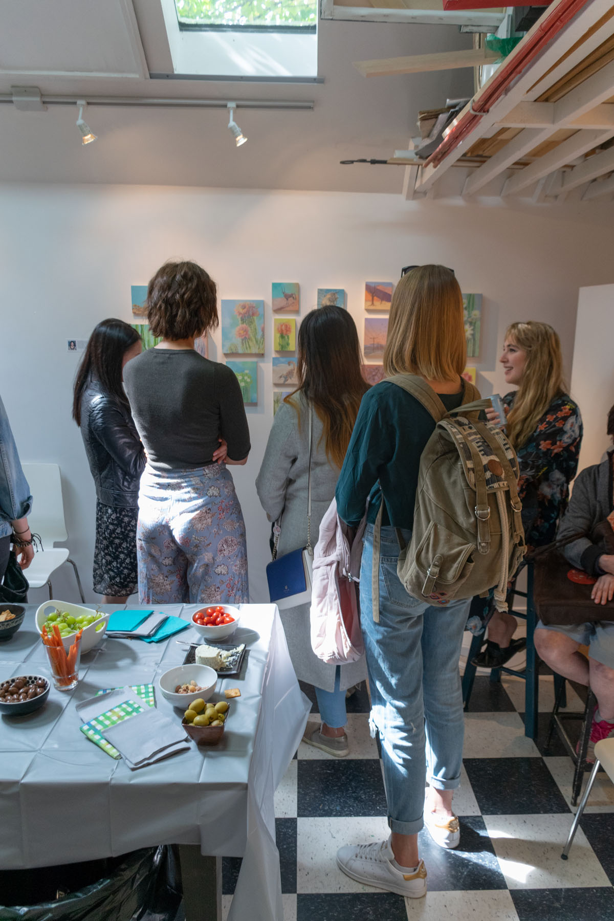 Visitors admiring Jominca's work during the show