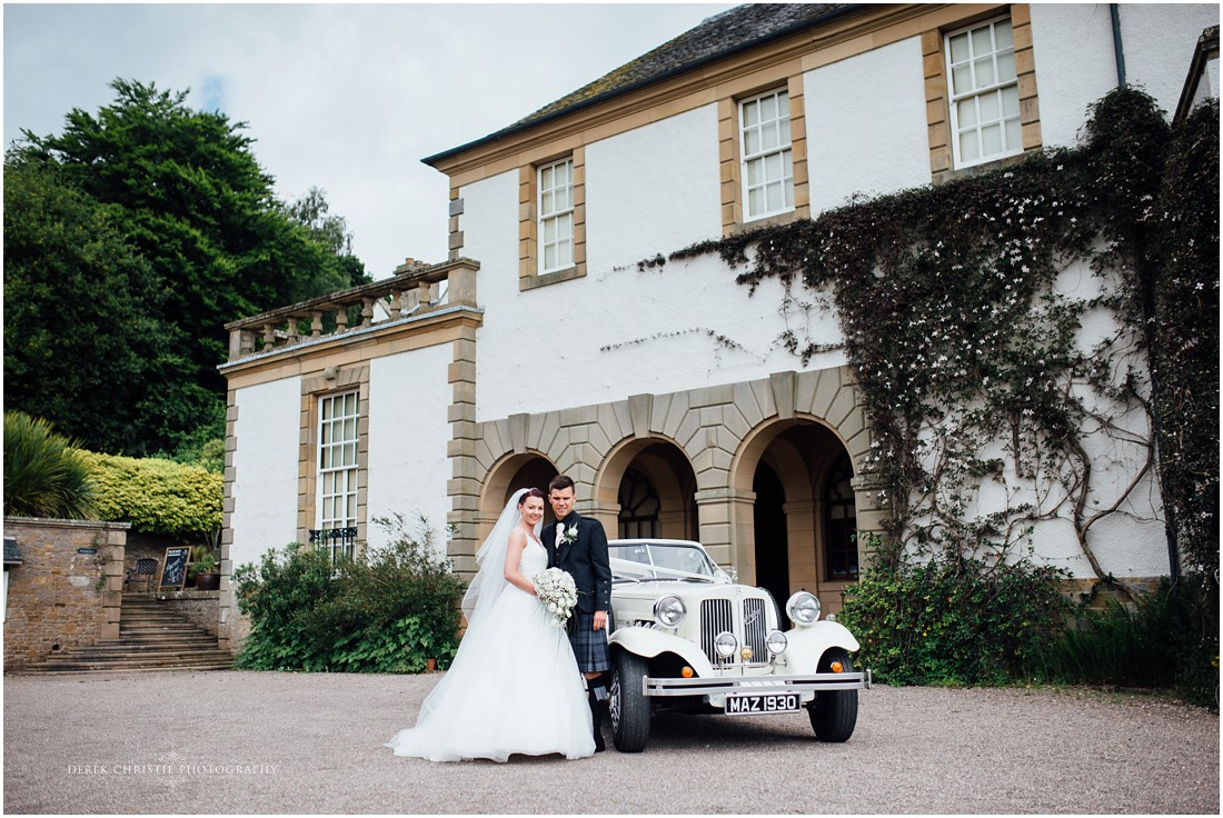 Emma & Thomas with vintage car on their wedding day at Hill Of Tarvit.