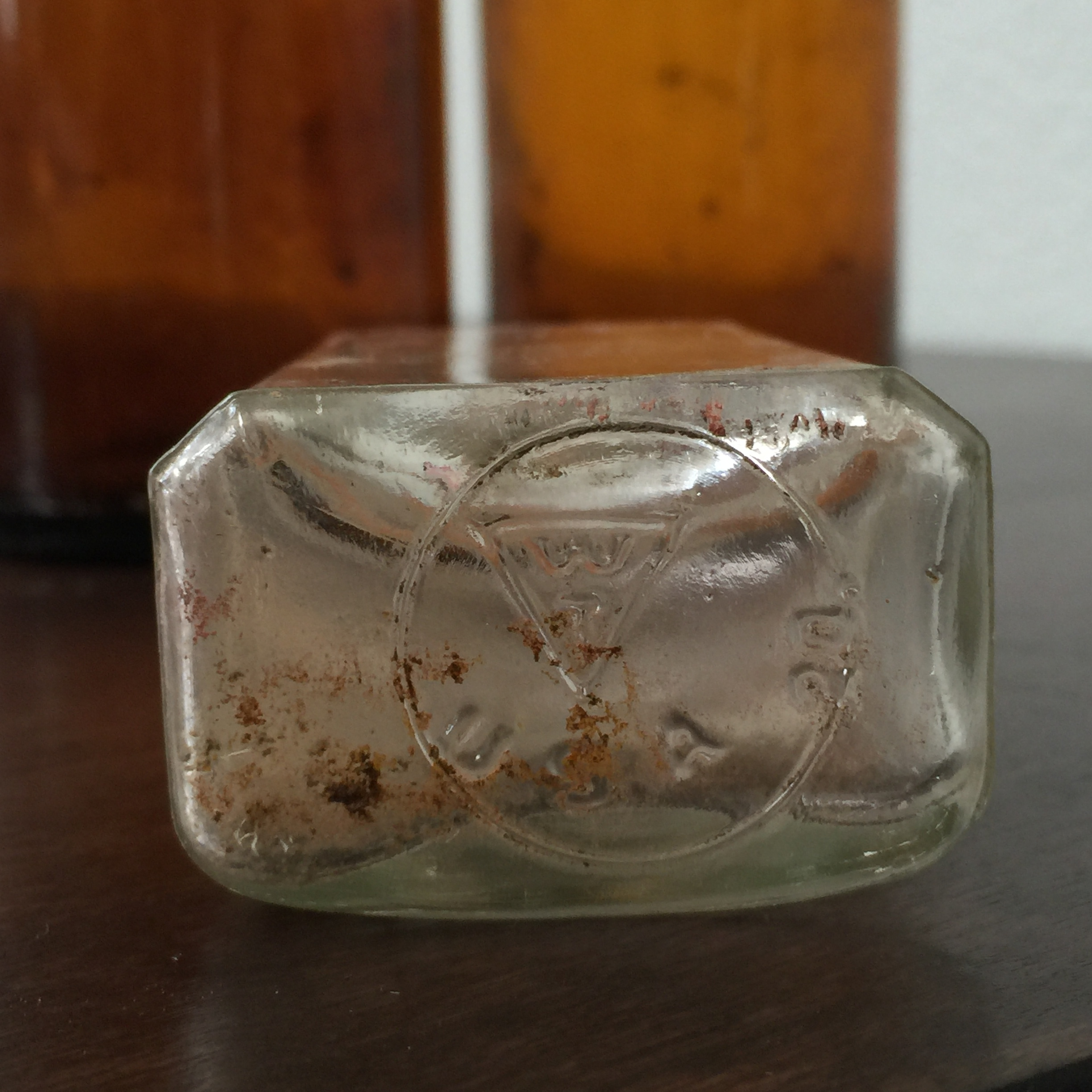 The base of the smaller, clear glass bottle with imprints indicating when and where it was manufactured.