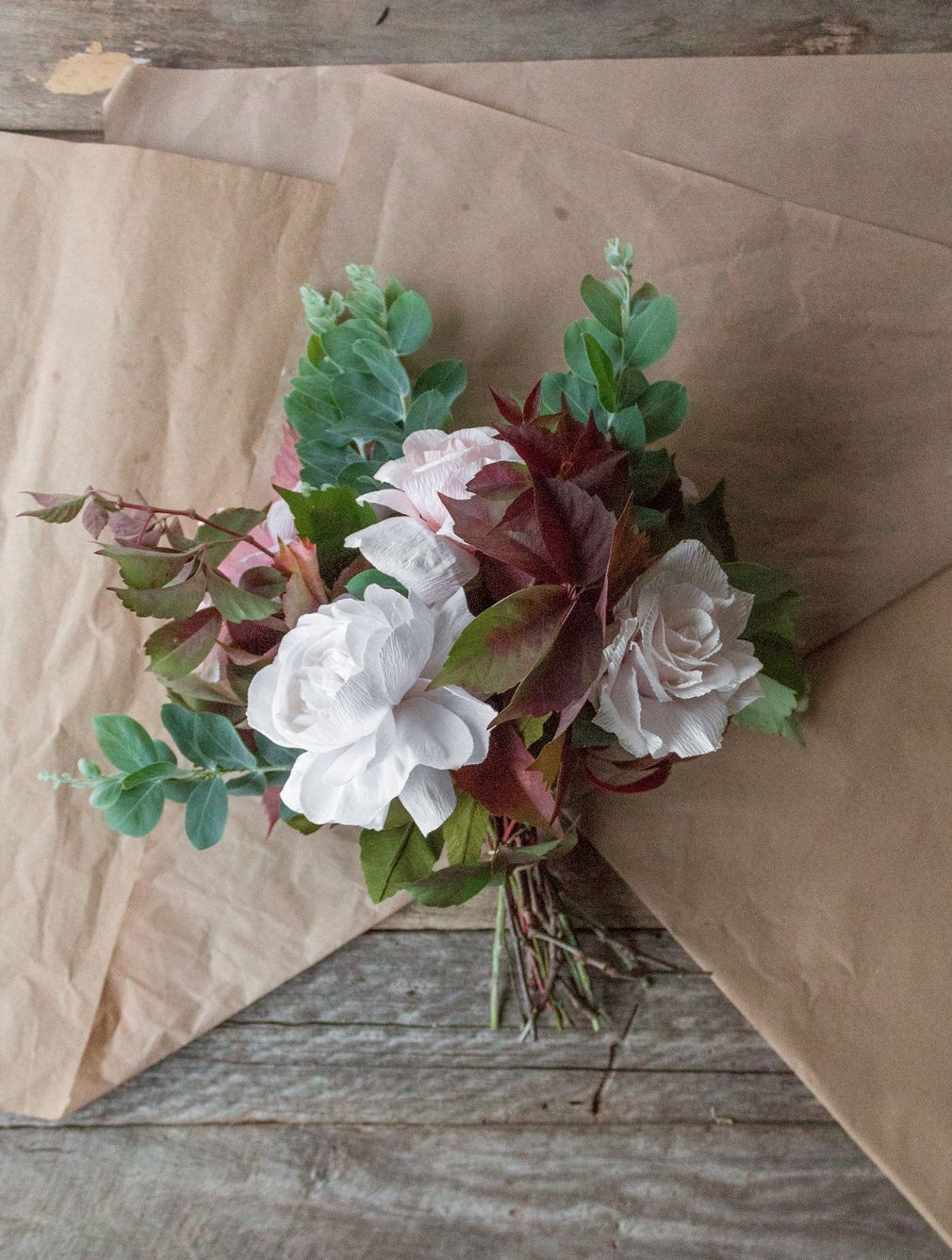 The bouquet ready to be wrapped with paper. The paper is placed down to make an upside down V. Source: Lisel Vonhoff from  @bellebouquets