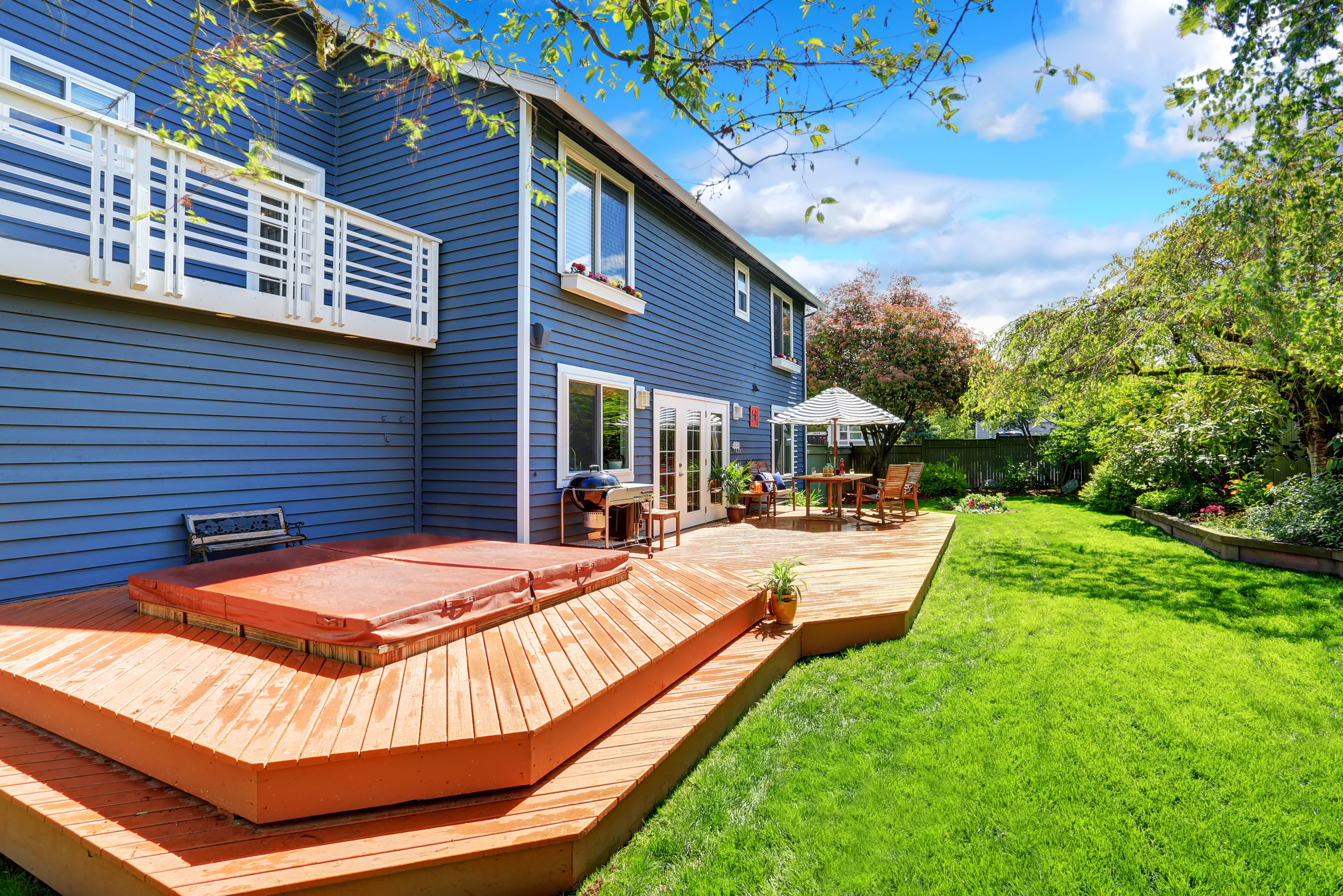 Large back deck with hot tub with blue house