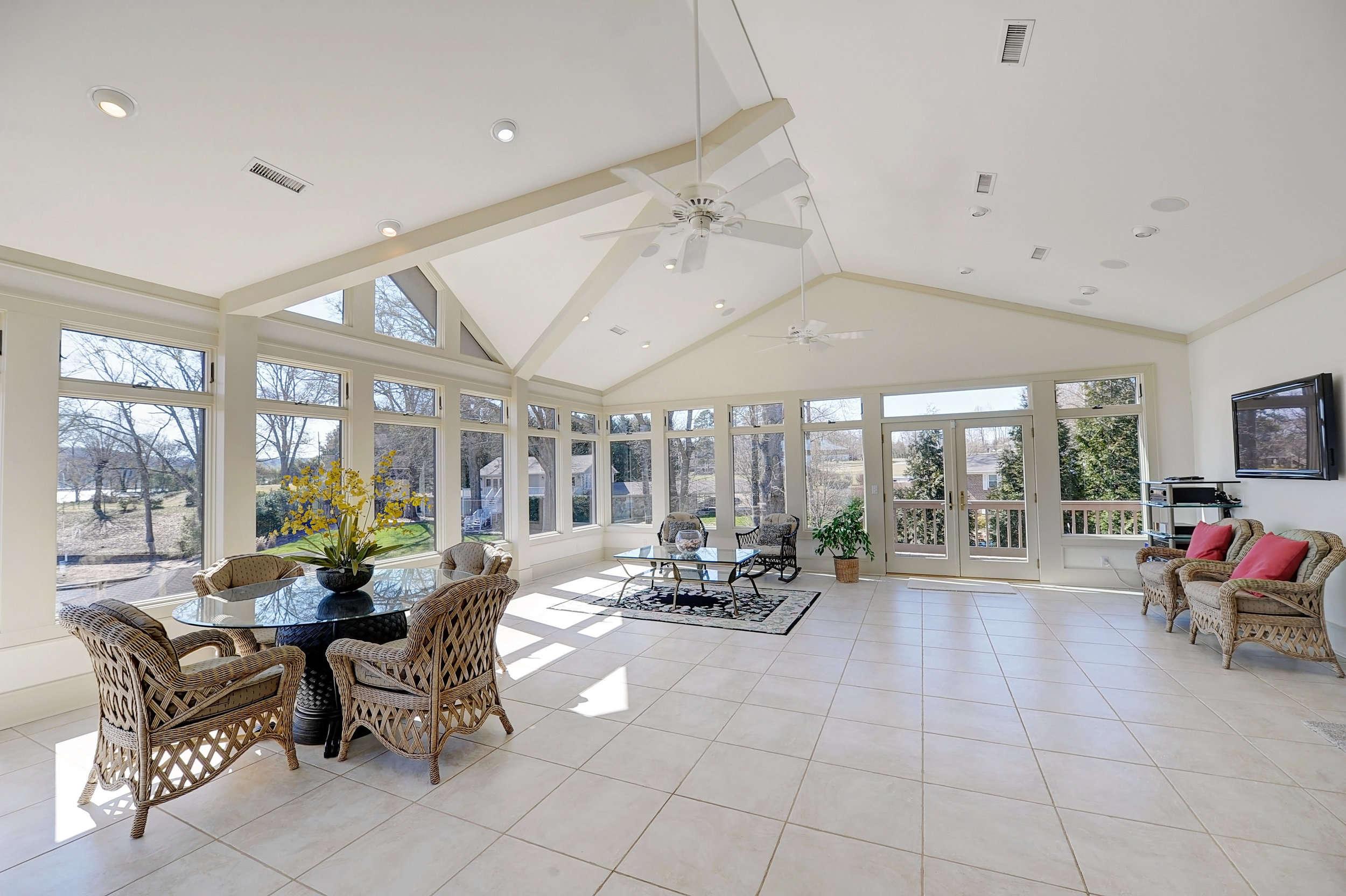 Large sunroom with white tile, rattan furniture, picnic table, fan, and TV